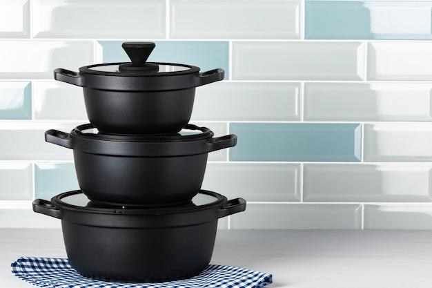 Set di pentole nere sul bancone della cucina vista frontale