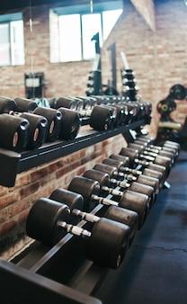 Set di manubri neri con manici in metallo su uno scaffale in palestra