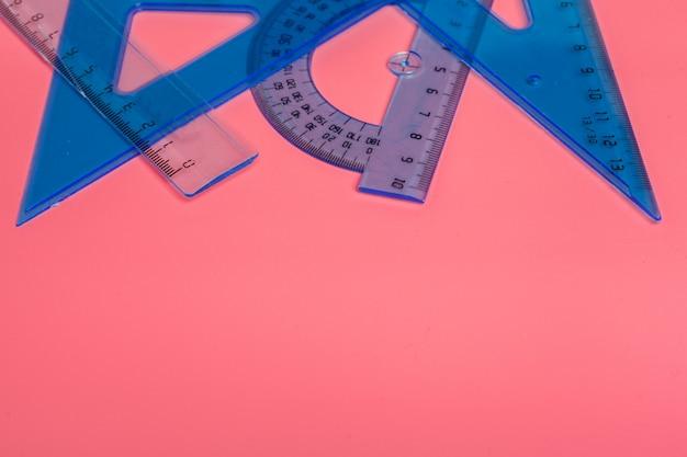 Insieme dei righelli di scuola blu sulla vista superiore rosa