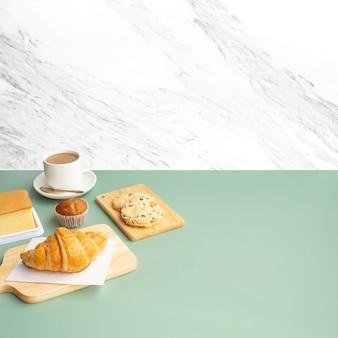Set di cibo per la colazione o panetteria, torta sul fondo della parete di marmo della cucina della tavola bianca.