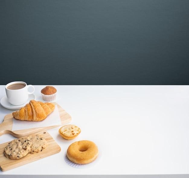 Set di cibo per la colazione o prodotti da forno e caffè sul fondo della cucina del tavolo