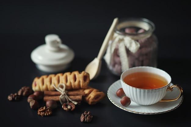 Preparato per la colazione. dolci e pasticcini con noci per il tè su sfondo nero. una tazza di caffè e polpette.