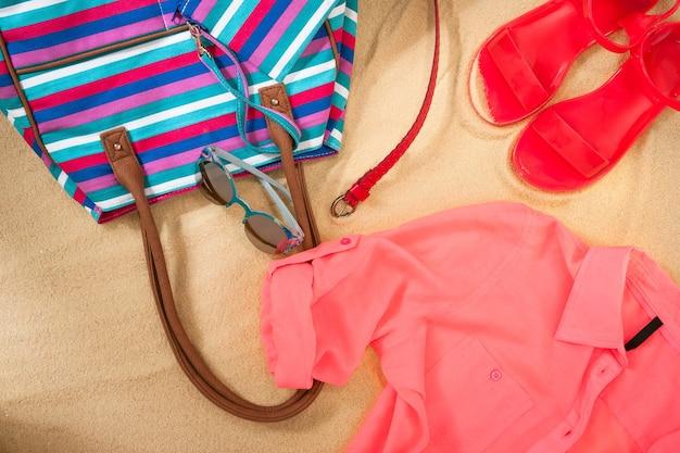 Set di abiti estivi luminosi per la spiaggia sulla sabbia dorata
