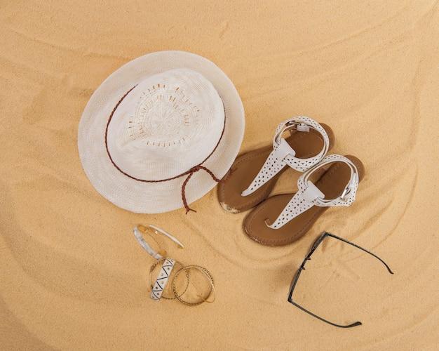 Un set di abiti estivi luminosi per la spiaggia sulla sabbia dorata