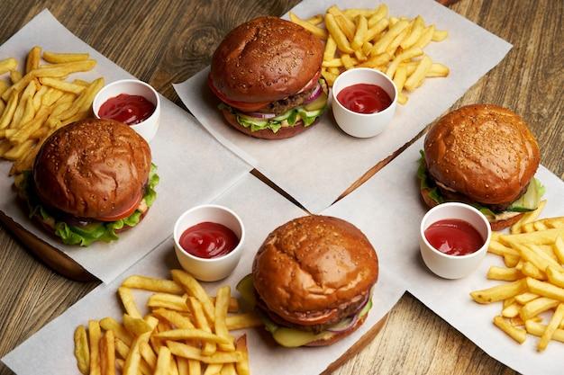 Set di hamburger con patatine fritte e salsa ketchup. grandi hamburger e patatine fritte sul fondo della tavola in legno. fast food impostare lo sfondo. menu di hamburger del ristorante