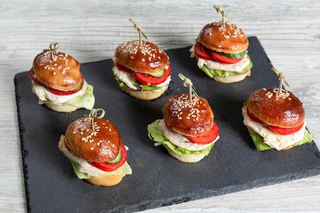 Set di hamburger di pollo a bordo nero sul tavolo di legno
