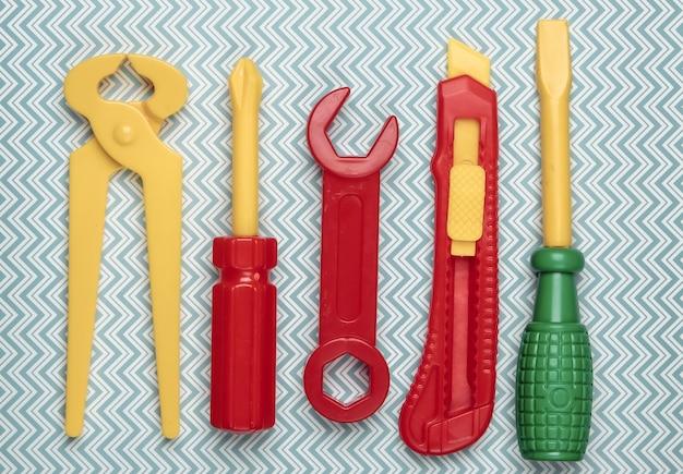 Set di strumenti di lavoro giocattolo per bambini su un blu. lay piatto.