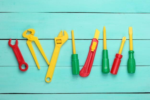 Set di strumenti di lavoro giocattolo per bambini su legno blu.