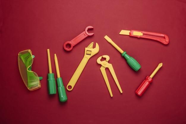 Set di strumenti di lavoro giocattolo per bambini su colore rosso.