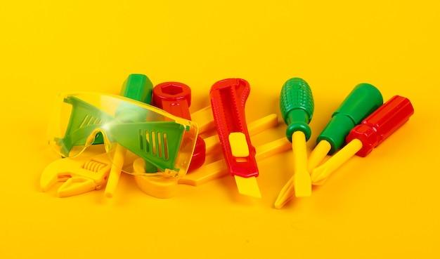 Set di strumenti di lavoro giocattolo per bambini su giallo.