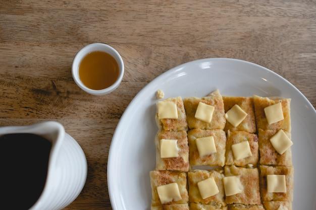 Set di tè cinese e pancake su un tavolo di legno.