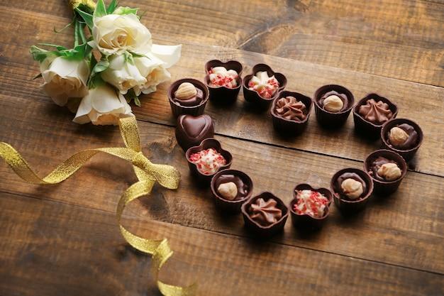 Set di cioccolatini che formano il cuore su un tavolo di legno