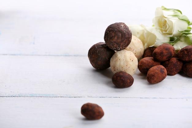 Set di cioccolatini con fiori su fondo in legno chiaro