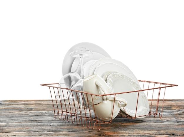 Set di piatti puliti sul tavolo contro il bianco
