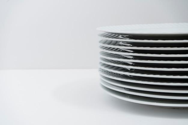 Set di piatti bianchi impilati puliti su un tavolo bianco. copia spazio