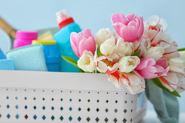Set di prodotti per la pulizia e fiori di primavera su sfondo colorato, primo piano