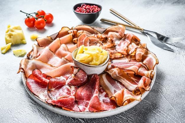 Set di salumi italiani prosciutto, prosciutto, pancetta, pancetta. sfondo bianco.