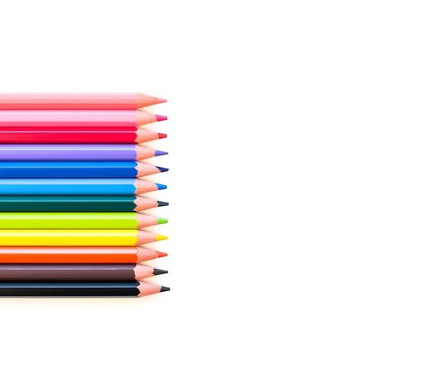 Una serie di matite colorate di tutti i colori dell'arcobaleno si trova orizzontalmente a sinistra in una riga. spazio vuoto a destra per il testo