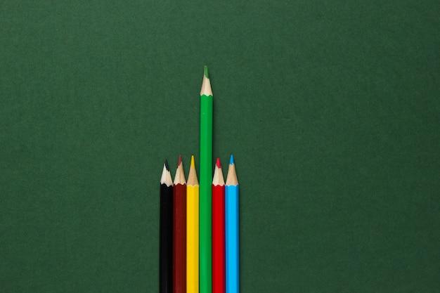 Set di matite colorate su superficie verde. concetto di unicità.