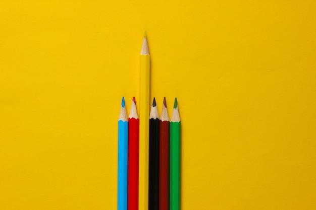 Set di matite colorate su superficie gialla. concetto di unicità.