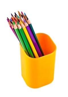 Set di matite di legno colorate in una tazza di plastica arancione intagliata isolata