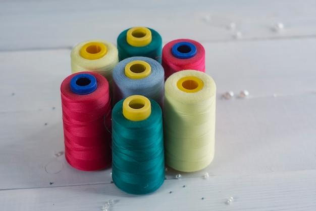 Set di palline colorate colorate di filo su uno sfondo di legno di colore chiaro.