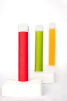 Set di colorate sigarette elettroniche usa e getta su un espositore su bianco