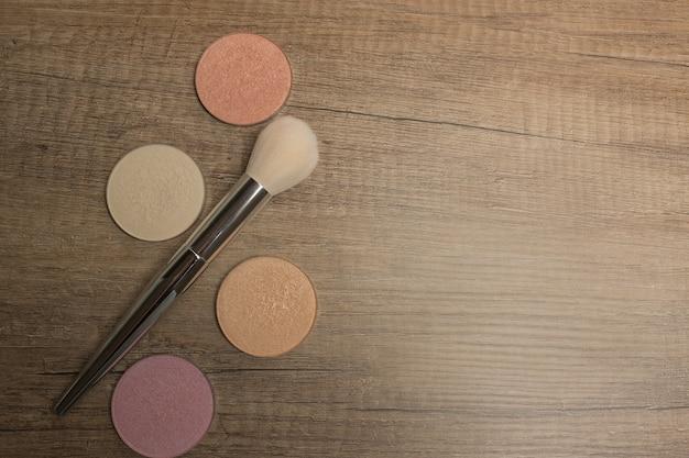 Set di evidenziatori colorati per il trucco con pennello cosmetico su uno sfondo di legno, spazio per il testo