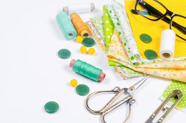 Set di tessuti colorati gialli e verdi, forbici, bottoni, bobine di filo e bicchieri