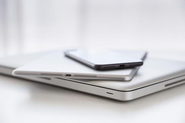 Set di un computer, un tablet e uno smatphone contro la scrivania bianca