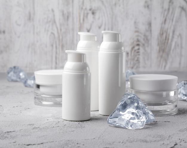 Set di bottiglie di crema cosmetica con ghiaccio sul tavolo grigio