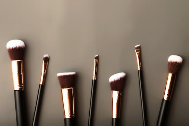 Set di pennelli cosmetici per il trucco collezione di accessori di bellezza su sfondo grigio