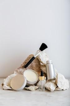 Set di prodotti cosmetici in confezione di alluminio. prodotti cosmetici zero waste per la cura della pelle su piedistallo in pietra dai colori pastello. estetica minimale.