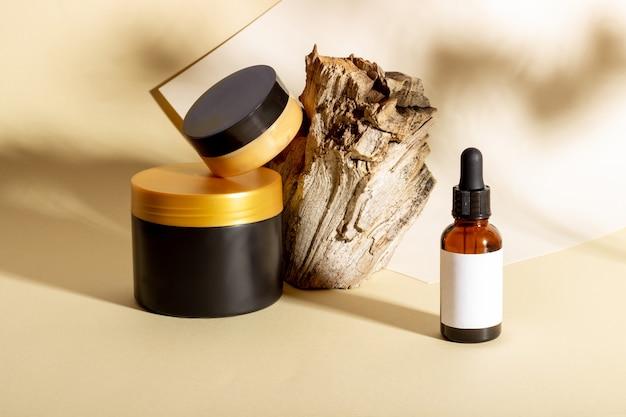 Una serie di prodotti cosmetici accanto a un tronco e ombre dure su uno sfondo beige. cosmetici biologici naturali