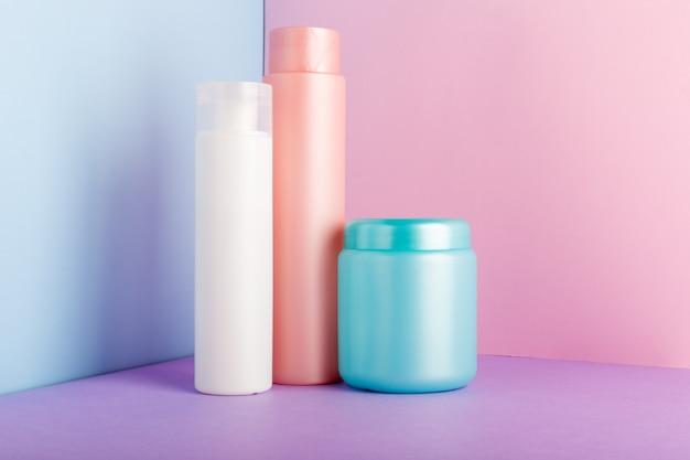 Set di prodotti cosmetici su sfondo rosa. collezione di pacchetti cosmetici per shampoo, maschera, balsamo, gel doccia.