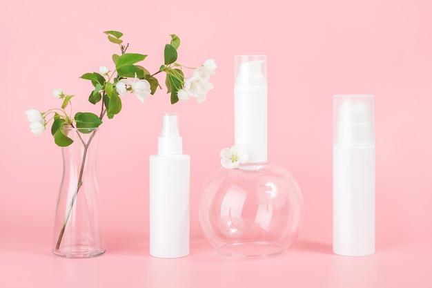Set di cosmetici per la cura della pelle viso, corpo. flaconi e tubo cosmetici in bianco bianchi sul podio di vetro