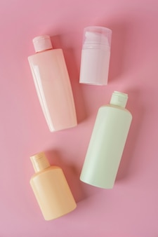 Set di prodotti cosmetici per la cura della pelle, prodotto per il viso, confezione di bottiglie vuote per la cura della pelle su sfondo rosa. concetto di bellezza e spa.
