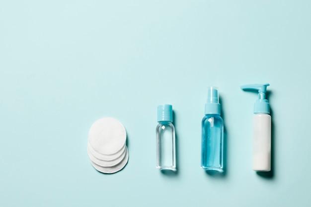 Set di cosmetici su sfondo blu. disposizione piatta.