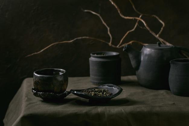 Set di teiera artigianale in ceramica nera fatta a mano, bollitore, brocca, barattolo con foglie di tè, tazza wabi sabi, piattino per la cerimonia del tè in piedi su tovaglia di lino con ramo secco in camera oscura.
