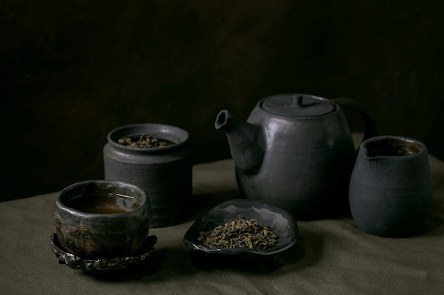Set di teiere e tazze in ceramica fatte a mano artigianali con sfondo scuro