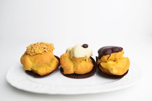 Set di bignè alla crema isolati su sfondo bianco. pasticceria francese con crema e salsa al cioccolato.