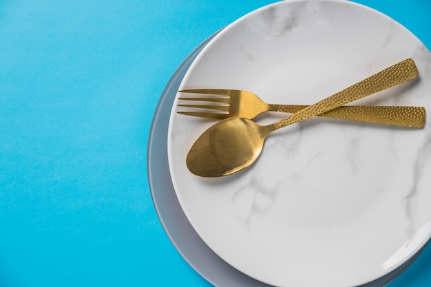 Set di posate cucchiaio, forchetta, piatto, isolato sulla parete blu. piatto in marmo bianco. vista dall'alto. impostazione da tavola con argenteria in oro. stile elegante luogo di ristorazione