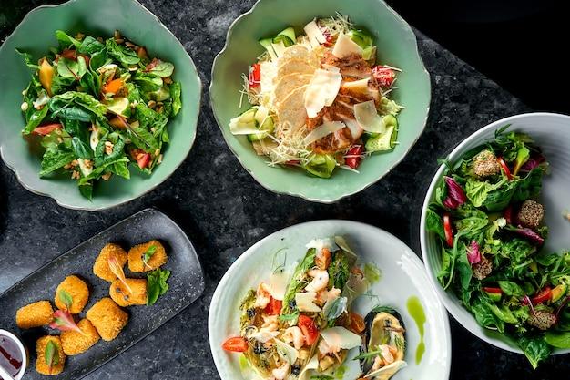 Una serie di deliziose insalate che serve ristorante su un tavolo di marmo scuro. cibo del ristorante. vista dall'alto