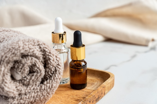 Set di diverse bottiglie con siero di bellezza, acido ialuronico e vitamine sul vassoio in legno con asciugamano.