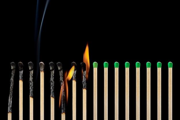 Insieme di diversi fiammiferi bruciati con fumo su sfondo nero. concetto di rispetto delle distanze sociali