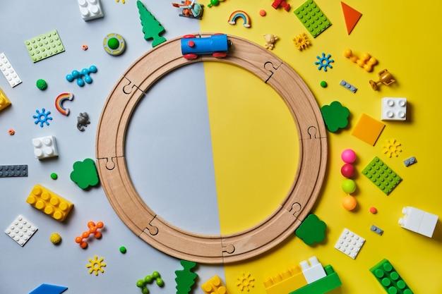 Set di diversi giocattoli per bambini, rotondi fatti di binari di legno, treno, costruttore su una superficie gialla e blu