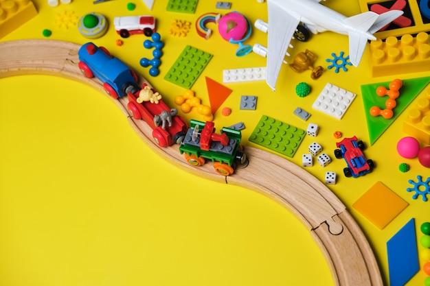 Set di diversi giocattoli per bambini, ferrovia in legno, treno, costruttore su sfondo giallo con spazio per la copia per il testo. vista dall'alto, piatto.