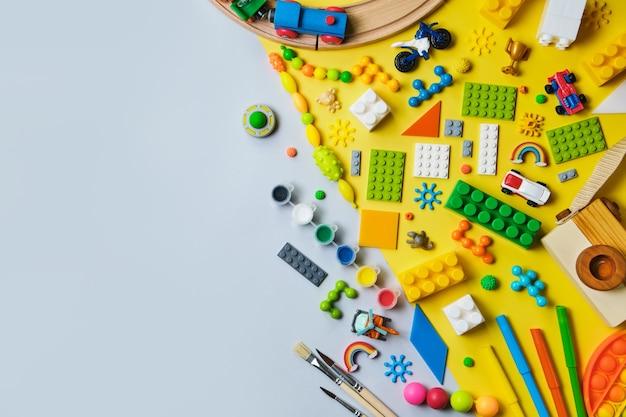 Set di diversi giocattoli per bambini, ferrovia in legno, treno, costruttore su una superficie gialla e blu
