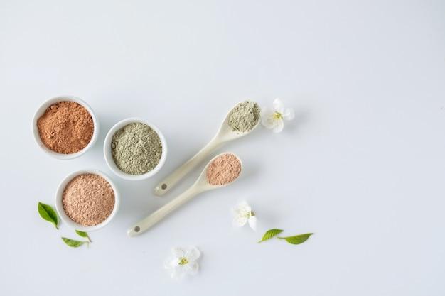 Insieme delle polveri di fango cosmetiche differenti dell'argilla su fondo bianco