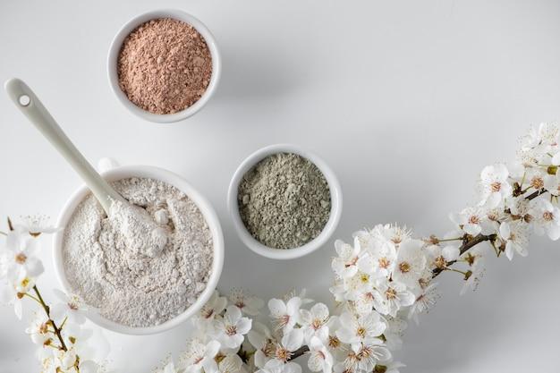 Set di diverse polveri di fango cosmetico argilla sulla superficie bianca